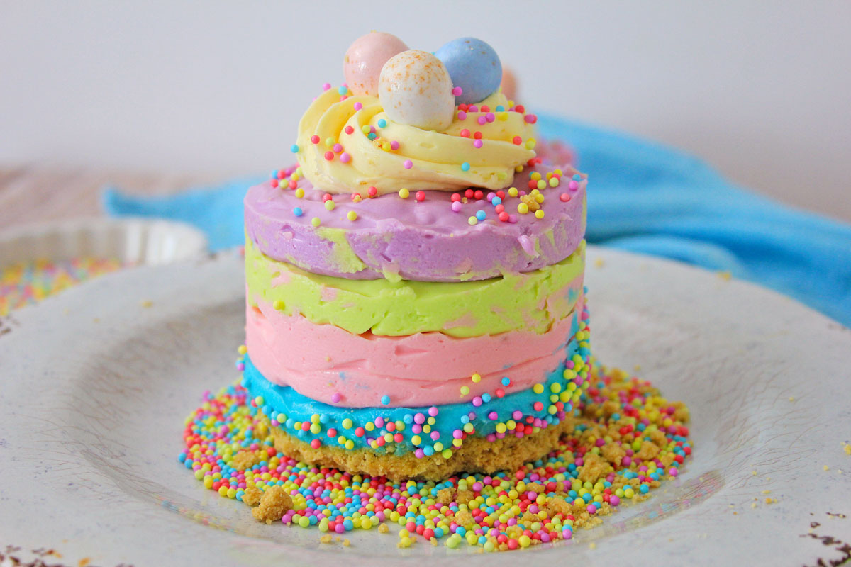 blue, pink, green and purple layers of no bake cheesecake with Cadbury eggs.