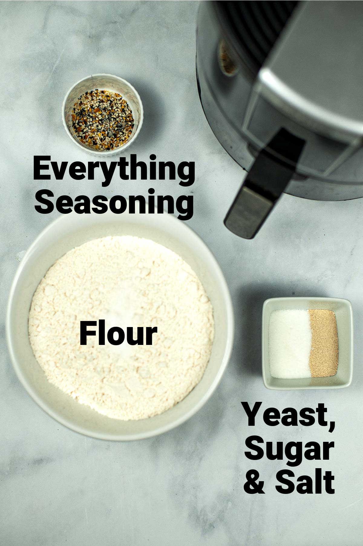 top down view of the ingredients including flour, yeast, sugar salt and seasoning.