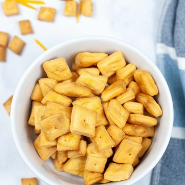 bowl of freshly air fried cheez-its and some sprinkled on the counter.