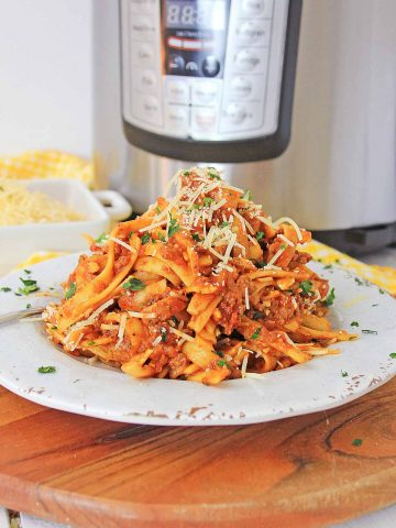 large serving of bolognese on a cutting board in front of the instant pot.