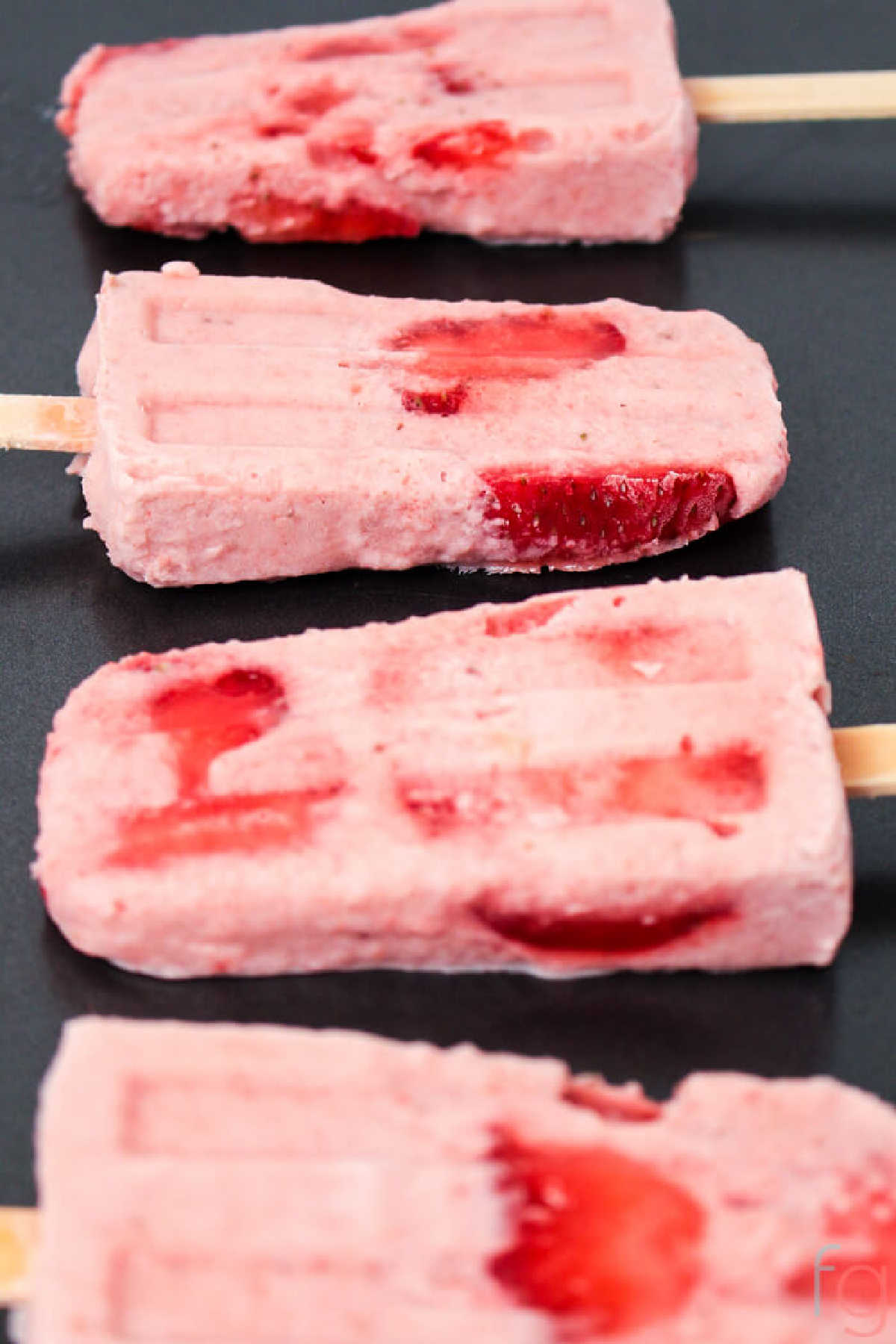 frozen strawberry banana smoothie popsicles on a dark background.
