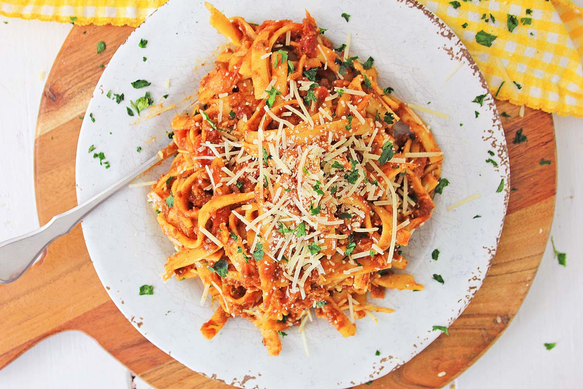 top down view of a plate of pasta and meat sauce with fresh grated cheese on top.