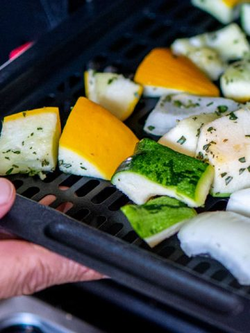 adding an air fryer tray with chopped squash and onions.