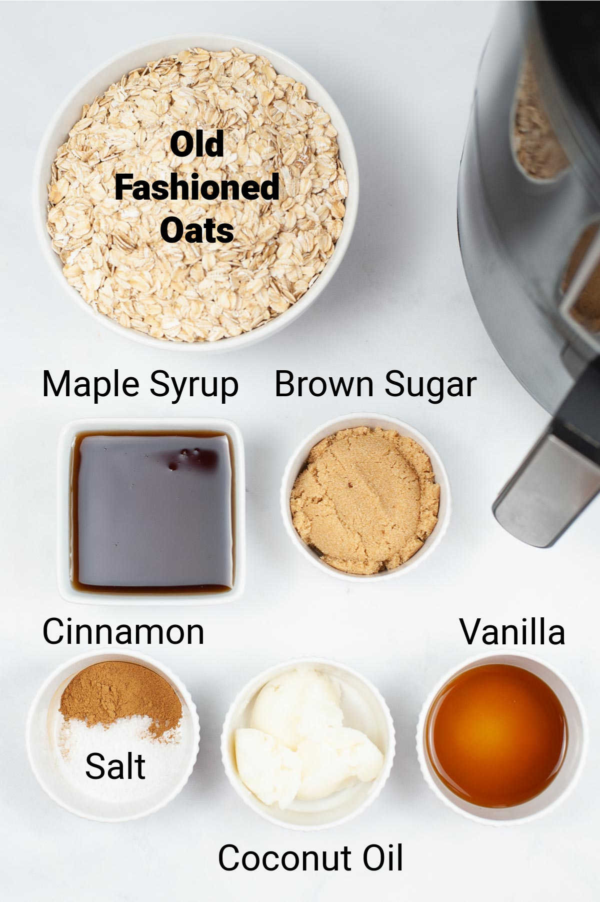 ingredient photo showing oats, cinnamon, syrup, sugar, vanilla and coconut oil on the table with labels.