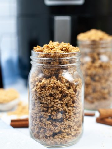 jar of granola in front of the air fryer with cinnamon sticks and brown sugar in the background.