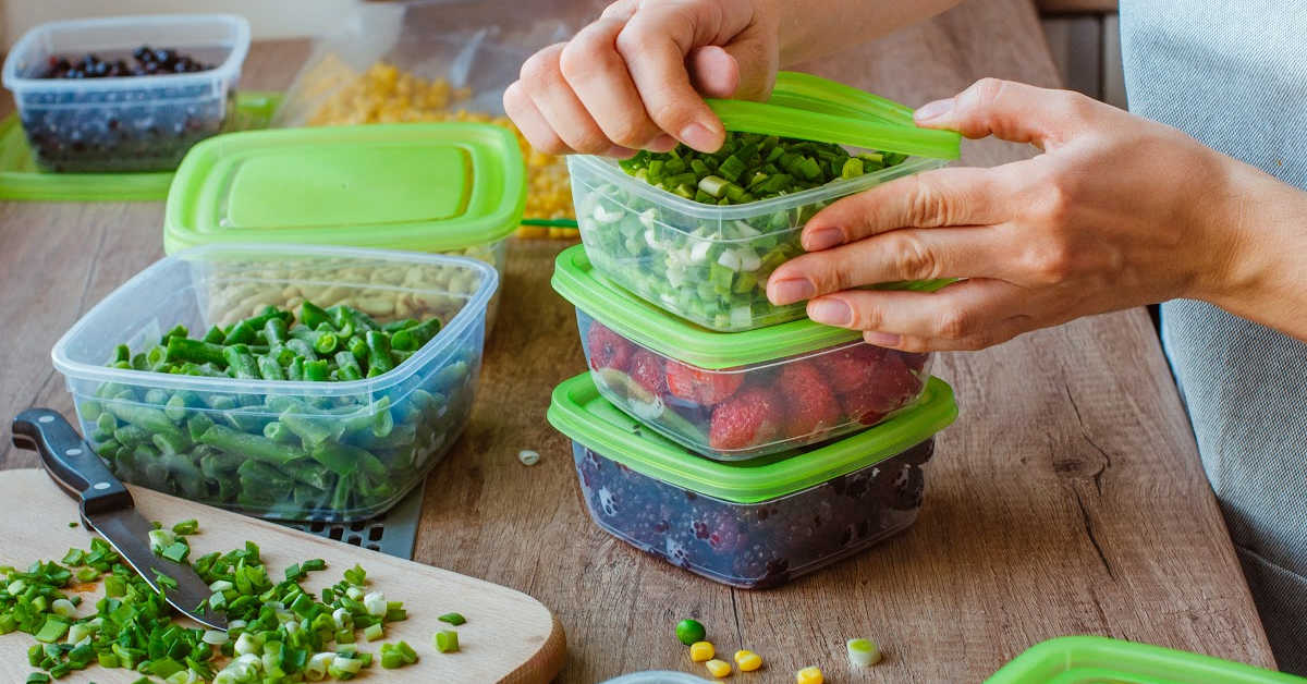 stacking meal prep containers filled with freshly chopped fruit and veggies.