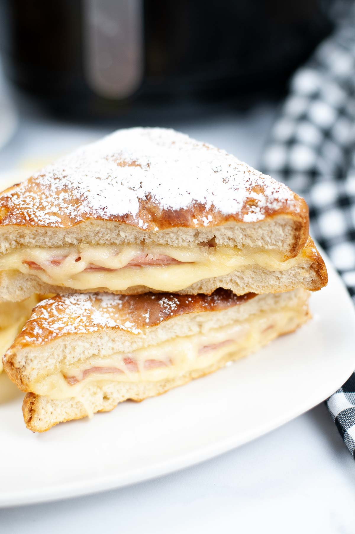 sliced monte cristo sandwich on a white plate with potato chips.
