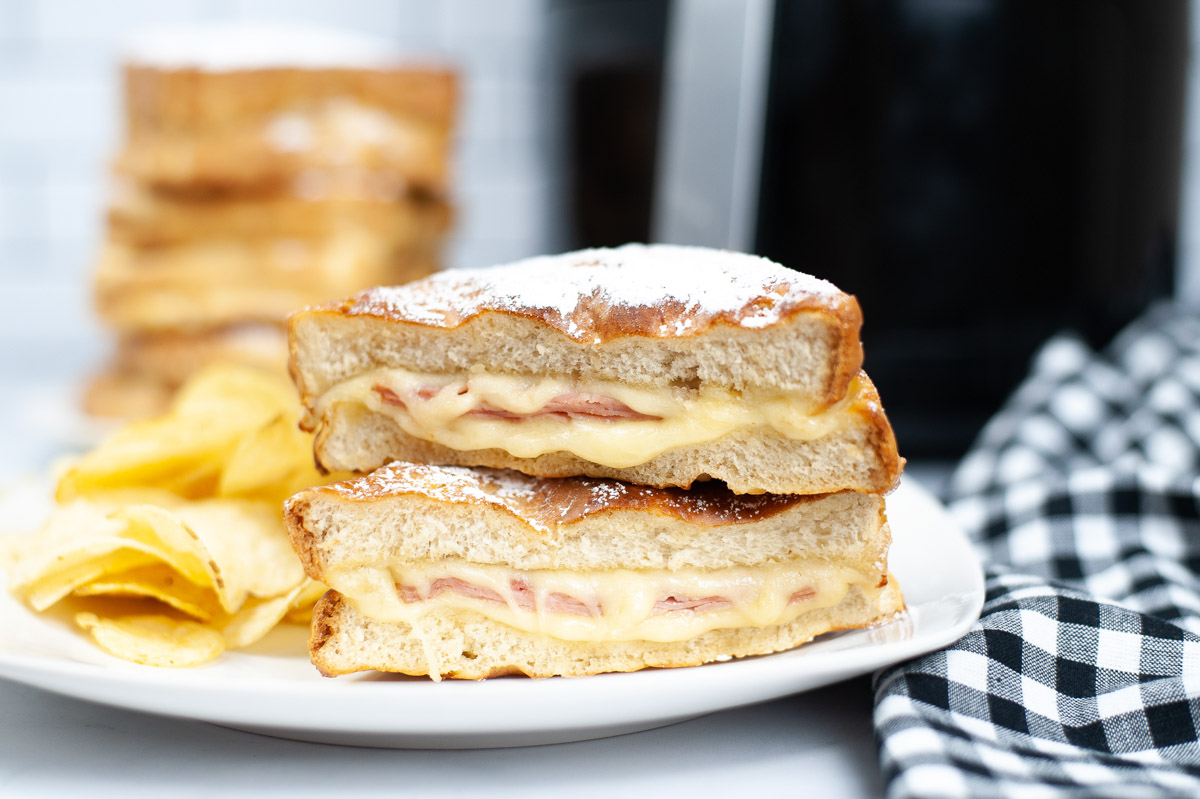 monte cristo sandwich sliced in half with powdered sugar and dripping Swiss cheese.