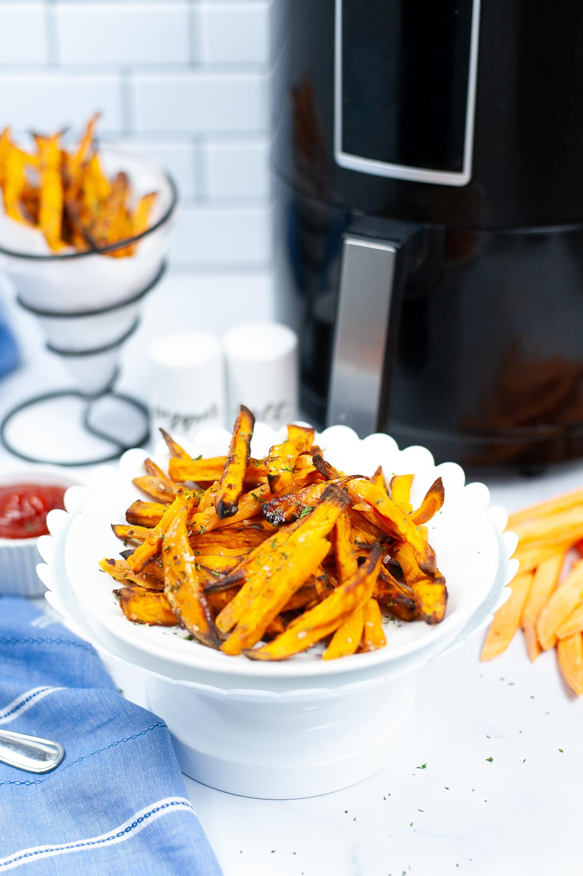 bowl of sweet potato fries straight from the air fryer and serving dish with ketchup.