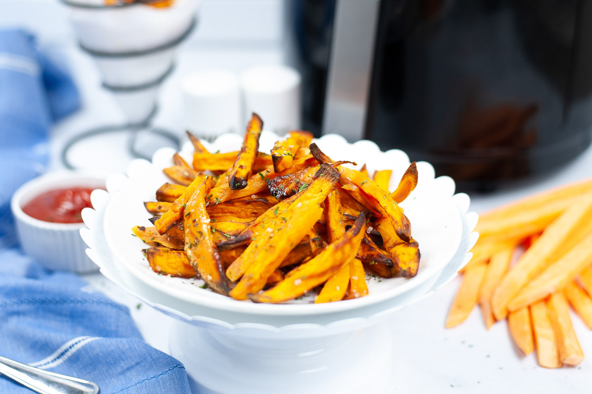 bowl of fries with slices sweet potatoes and ketchup in the background.