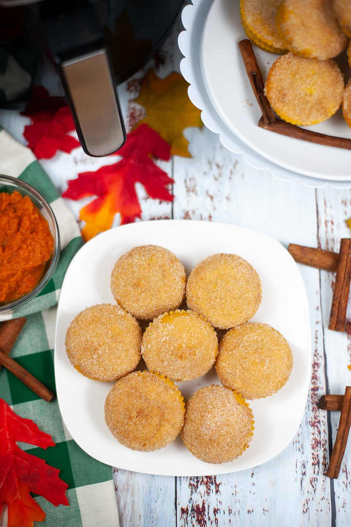 white plate with pumpkin muffins on it and fall decor on the table.