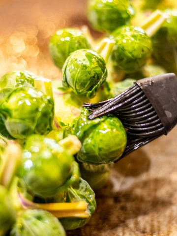 stalk loaded with fresh brussel sprouts and being brushed with an olive oil mix.