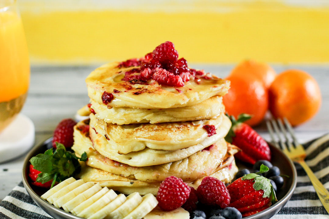 stack of pancakes on a plate in front of a yellow wall.