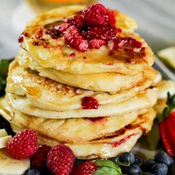 stack of ricotta pancakes with blueberries, raspberries, strawberries and bananas on a plate
