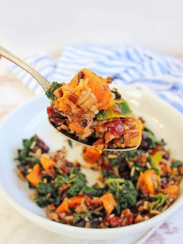 spoon filled with wild rice, craisins, sweet potato, kale and other veggies.
