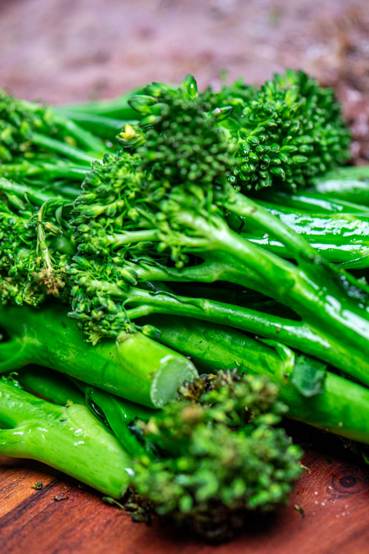 stack of broccolini made in the air fryer on a cutting board.
