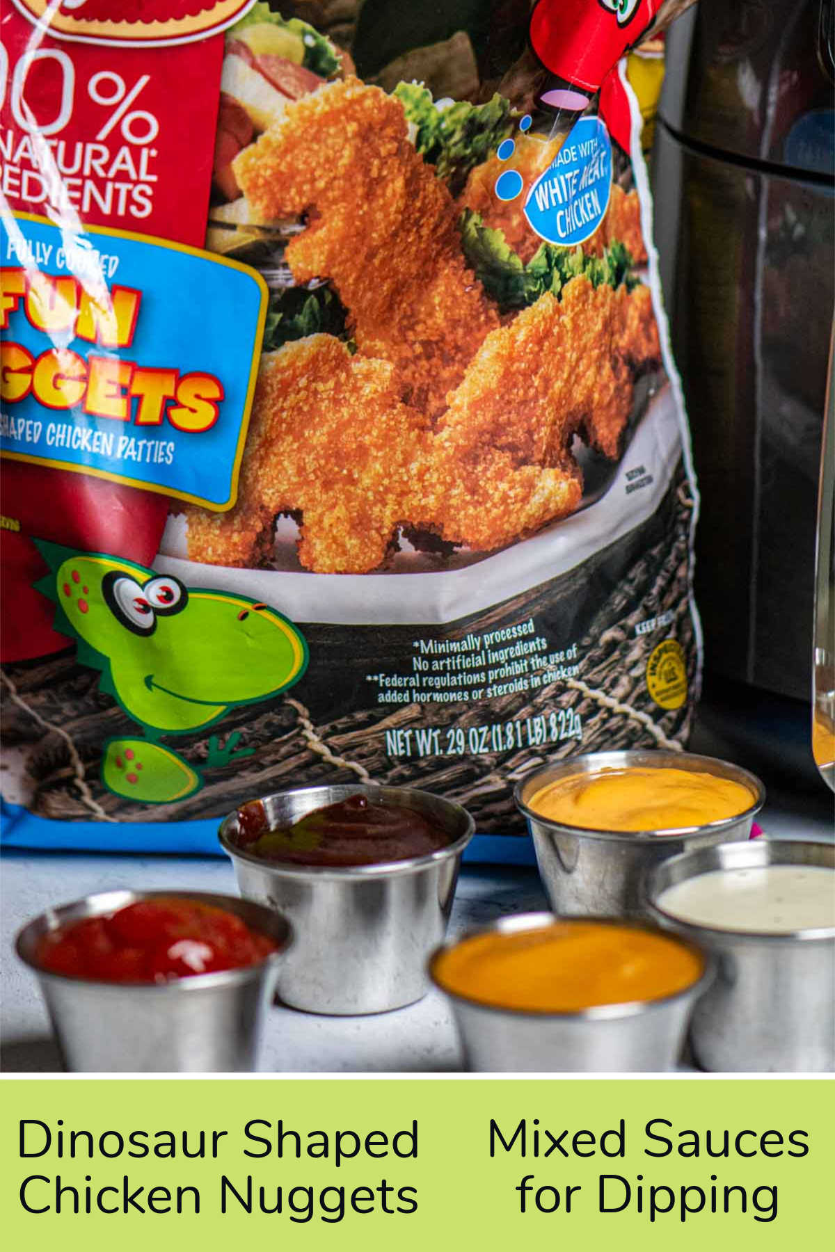 ingredient photo showing a bag of frozen dino nuggets and ramekins filled with dipping sauces in front of the air fryer.