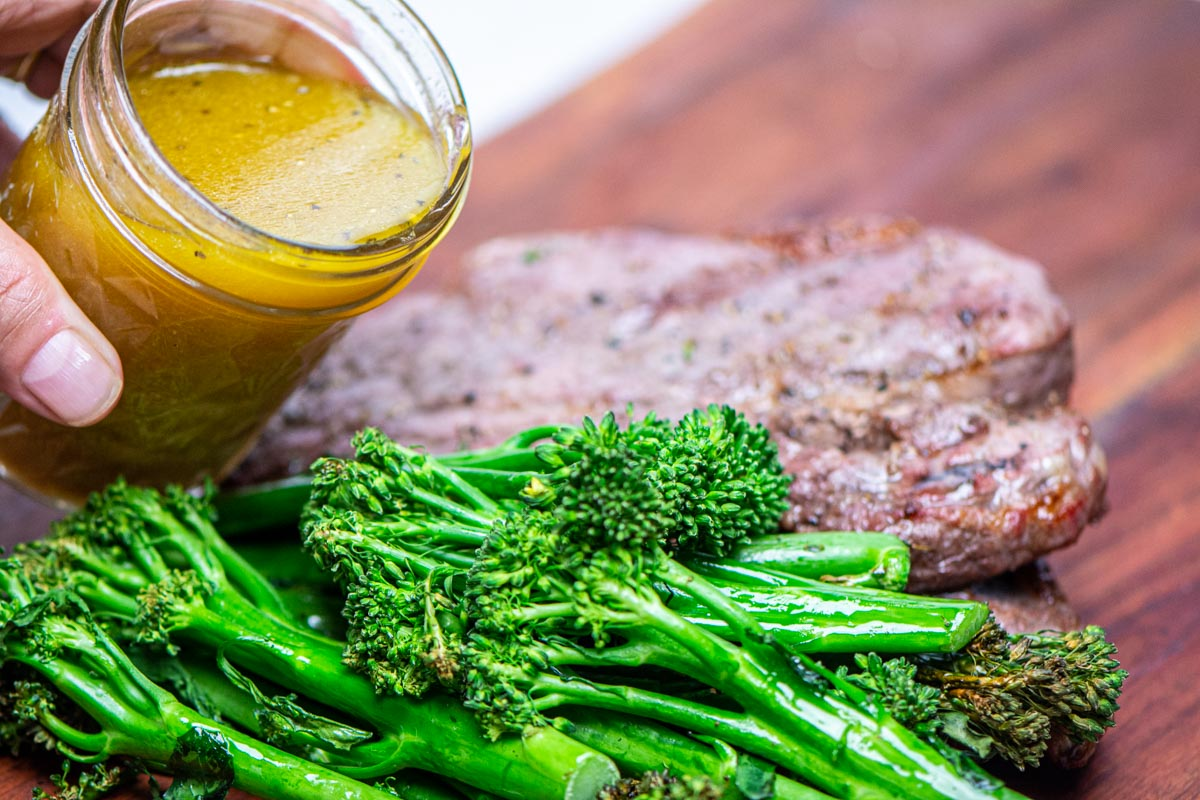 pouring the vinaigrette over the broccolini on a wooden cutting board.